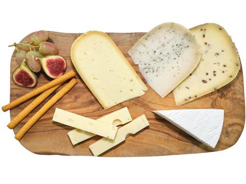 Verschiedene Käsesorten aus Kuh-, Schafs und Ziegenmilch, angerichtet auf einem Olivenholzbrett
