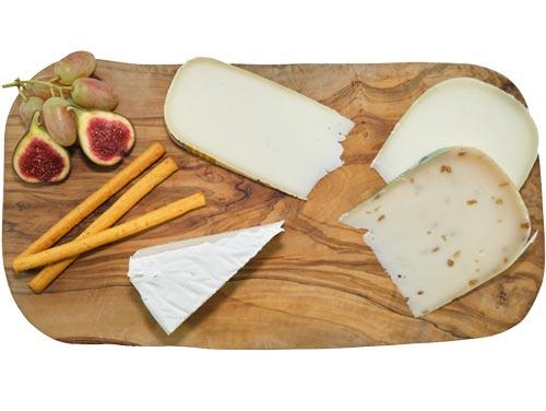 Verschiedene Käsesorten aus Schafs- und Ziegenmilch, angerichtet auf einem Olivenholzbrett