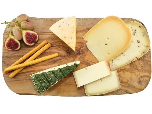 Verschiedene Käsesorten aus Kuhmilch, angerichtet auf einem Olivenholzbrett